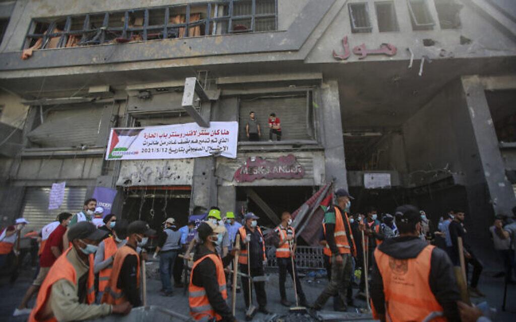 متطوعون فلسطينيون يزيلون الأنقاض في شارع بمدينة غزة، بعد أن أصابته غارات جوية إسرائيلية أثناء عملية 'حارس الأسوار'، 23 مايو، 2021. (Atia Mohammed / Flash90)