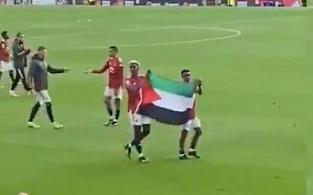 لقطة شاشة من مقطع فيديو للاعبي مانشستر يونايتد يحملان العلم الفلسطيني بعد مباراة، 17 مايو، 2021. (Twitter)