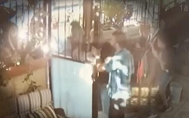 """لقطة شاشة من مقطع فيديو بثته محطة """"كان"""" العامة للحظة التي أصيبت فيها جنى الكسواني في ظهرها برصاصة مطاطية أطلقها ضابط شرطة خارج منزلها في حي الشيخ جراح في القدس.  (Screen capture: Twitter)"""