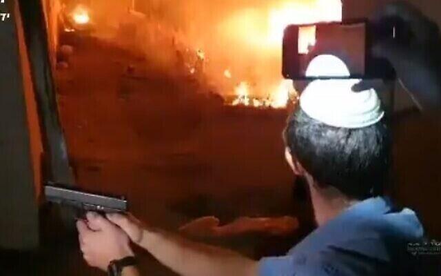 إسرائيلي يسحب مسدسه بعد اشعال النار في سيارة خلال اشتباكات في حي الشيخ جراح في القدس الشرقية، 6 مايو 2021 (Screencapture / Twitter)