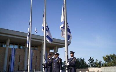 حرس الكنيست ينكس الأعلام الإسرائيلية إلى نصف السارية خارج الكنيست في القدس مع بدء يوم حداد وطني على ضحايا كارثة ميرون، 2 مايو 2021.  (Noam Moskowitz/Knesset)