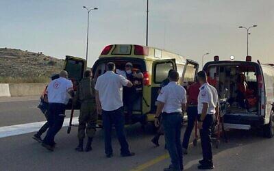 مسعفون ينقلون ضحايا هجوم إطلاق نار من سيارة عابرة في شمال الضفة الغربية إلى سيارة إسعاف، 2 مايو، 2021. (Magen David Adom)