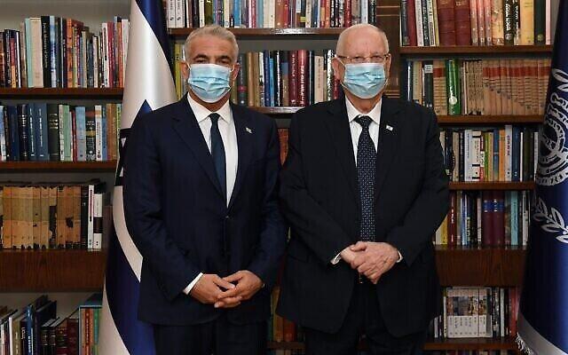 الرئيس رؤوفين ريفلين (من اليمين) يلتقي بزعيم حزب يش عتيد يائير لابيد في مقر رؤساء إسرائيل في القدس، 5 مايو، 2021. (Haim Zach / GPO)