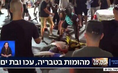 رجل يعتدي بالضرب على شخص ممدد على الأرض في مدينة بات يام الإسرائيلية وسط أعمال عنف عرقية في جميع أنحاء إسرائيل، 12 مايو، 2021. (Screenshot)