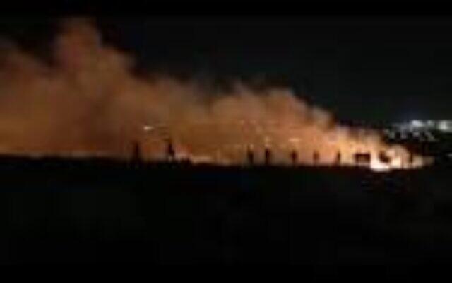 فلسطينيون يحاولون إخماد نيران أشعلها كما يُزعم مستوطنون خارج قرية جالود في شمال الضفة الغربية، 3 مارس، 2021. (Screen Capture: B'Tselem)
