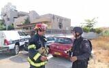 مسؤولو خدمة الإطفاء خارج كنيس في أشكلون أصيب بصاروخ، 16 مايو، 2021. (National Fire and Rescue Authority)