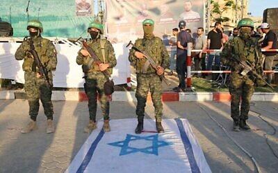 أعضاء من الجناح العسكري لحركة حماس يقفون على العلم الإسرائيلي في خان يونس ، جنوب قطاع غزة في 27 مايو، 2021، في الوقت الذي تعلن فيه حماس انتصارها بعد 11 يوما من الصراع مع إسرائيل. (SAID KHATIB / AFP)