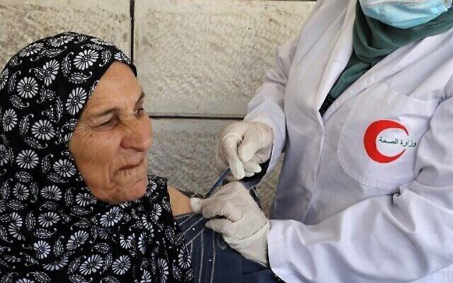 عاملة صحة فلسطينية تقوم بتطعيم مسنة فلسطينية ضد فيروس كورونا، في قرية دورا بالقرب من الخليل بالضفة الغربية، 9 حزيران 2021. (HAZEM BADER / AFP)