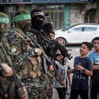 طفال فلسطينيون يصطفون للتسجيل في مخيم صيفي نتظمه كتائب عز الدين القسام، الجناح العسكري لحركة حماس، في مدينة غزة، 14 يونيو،  2021. (MAHMUD HAMS / AFP)