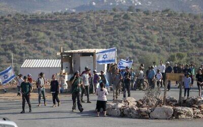 مستوطنون إسرائيليون يرفعون الأعلام الإسرائيلية في بؤرة إفياتار الاستيطانية غير القانونية في الضفة الغربية، 21 يونيو، 2021. (Ahmad Gharabli / AFP)