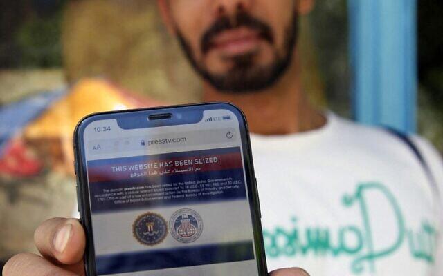 """رجل إيراني يظهر على هاتفه المحمول بيانا يعلن فيه أن الموقع الإلكتروني لمحطة 'برس تي في' التلفزيونية الإيرانية الناطقة بالإنجليزية """"تم الاستيلاء عليه من قبل حكومة الولايات المتحدة"""" ، في العاصمة طهران في 23 يونيو، 2021.(Photo by - / AFP)"""