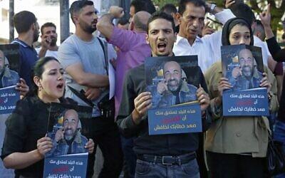 فلسطينيون يحملون ملصقات تصور الناشط الحقوقي نزار بنات، خلال مظاهرة اندلعت  في أعقاب اعتقاله العنيف ووفاته في الحجز في بلدته الخليل بالضفة الغربية، 27 يونيو، 2021. (MOSAB SHAWER / AFP)