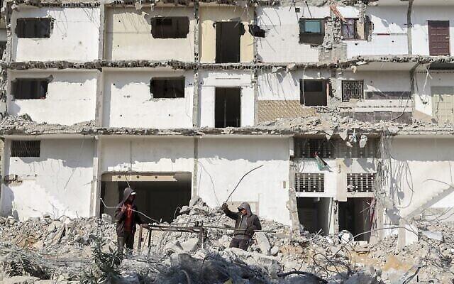 عمال فلسطينيون يعيدون تدوير قضبان معدنية من حطام مبنى دمرته الغارات الجوية الاسرائيلية خلال صراع استمر 11 يوما الشهر الماضي في مدينة غزة، 29 يونيو، 2021. (MOHAMMED ABED / AFP)