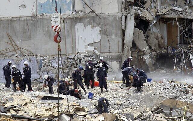 أعضاء فريق البحث والإنقاذ في جنوب فلوريدا يبحثون عن ناجين محتملين في مبنى 'تشامبلين' السكني المكون من 12 طابقًا والذي انهار جزئيا في 26 يونيو 2021 في سيرفسايد، فلوريدا. (Joe Raedle / Getty Images / AFP)