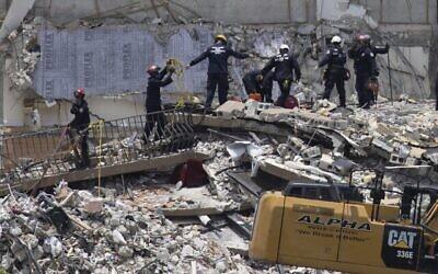 فرق الإنقاذ تبحث عن ناجين محتملين في برج تشامبلين السكني المكون من 12 طابقا والذي انهار جزئيا في 26 يونيو 2021، في سيرفسايد، فلوريدا.  (JOE RAEDLE / GETTY IMAGES NORTH AMERICA / Getty Images via AFP)