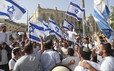 إسرائيليون يلوحون بالأعلام الإسرائيلية خلال مسيرة 'يوم  أورشليم القدس' في المدينة، 10 مايو، 2021. (AP Photo / Ariel Schalit)