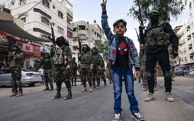 طفل يقف  مع مقاتلي حماس خلال استعراض في الشارع تكريما لباسم عيسى، أحد كبار قادة حماس ، الذي قُتل في العمليات العسكرية لقوات الدفاع الإسرائيلية قبل وقف إطلاق النار الذي تم التوصل إليه بعد حرب استمرت 11 يوما بين حركة حماس في غزة وإسرائيل، في مدينة غزة، 22 مايو، 2021. (AP Photo / John Minchillo)
