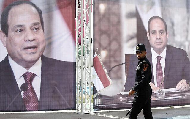 عنصر في شرطة حماس يسير أمام صور كبيرة للرئيس المصري عبد الفتاح السيسي، بينما يلتقي قادة حماس مع رئيس المخابرات المصرية عباس كامل في مدينة غزة، 31 مايو، 2021.  (Adel Hana/AP)