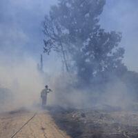 رجل إطفاء إسرائيلي يحاول إخماد حريق ناجم عن بالون حارق أطلقه فلسطينيون من قطاع غزة على حدود إسرائيل وغزة، 15 يونيو، 2021. (AP Photo / Tsafrir Abayov)