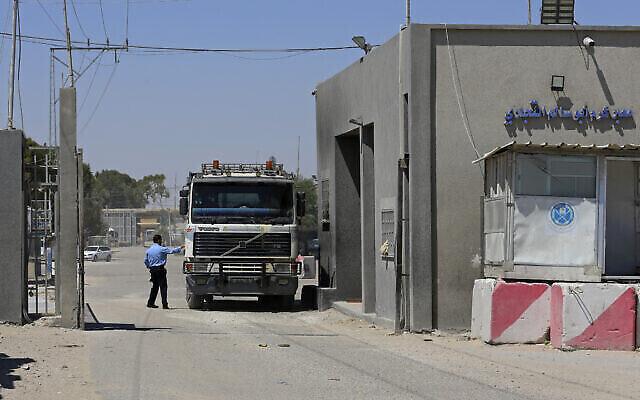 توضيحية: عنصر امن من حماس يفحص شاحنة دخلت غزة عند بوابة معبر كيرم شالوم  مع اسرائيل ، في رفح جنوب قطاع غزة، 21 يونيو، 2021.  (Adel Hana/AP)