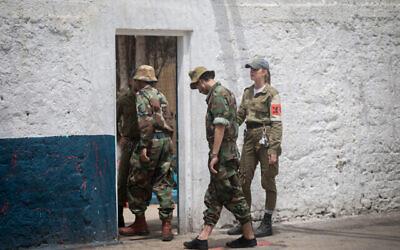 توضيحية: ضابطة في الشرطة العسكرية الإسرائيلية (على يمين الصورة)، تقتاد جنديين إسرائيليين مسجونين عبر باب في السجن رقم 4، وهو  أكبر سجن عسكري في إسرائيل، في قاعدة تسريفين العسكرية في وسط إسرائيل، 26 أبريل، 2018. (Miriam Alster / FLASH90)