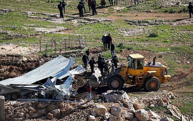 جرافة اسرائيلية تهدم سقيفة مزرعة فلسطينية في قرية مسافر يطا في الضفة الغربية، شباط 2020. (Wisam Hashlamoun / Flash90)