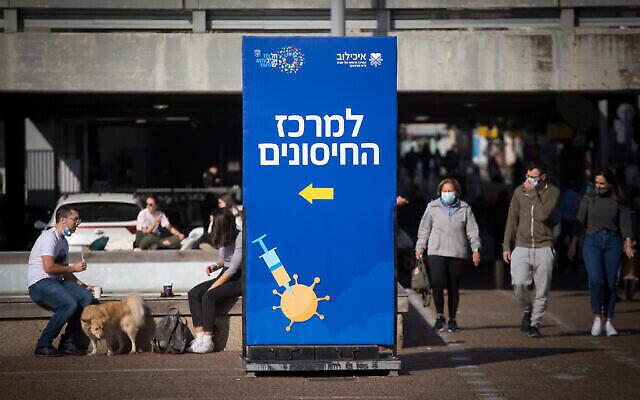 إسرائيليون يجلسون بالقرب من مركز تطعيم في ميدان رابين في تل أبيب، 31 ديسمبر، 2020. (Miriam Alster / Flash90)