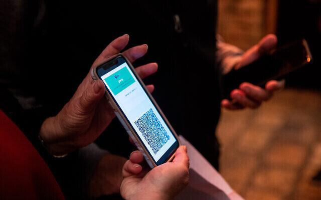 سيدة تعرض 'الجواز الأخضر' عند وصولها إلى مسرح في القدس، 23 فبراير، 2021. (Yonatan Sindel / Flash90)
