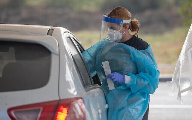 توضيحية: عاملة رعاية صحية تأخذ عينات مسحة من إسرائيليين في محطة اختبار  لتشخيص فيروس كورونا في مدينة الرملة، 18 أبريل، 2021. (Yossi Aloni / Flash90)
