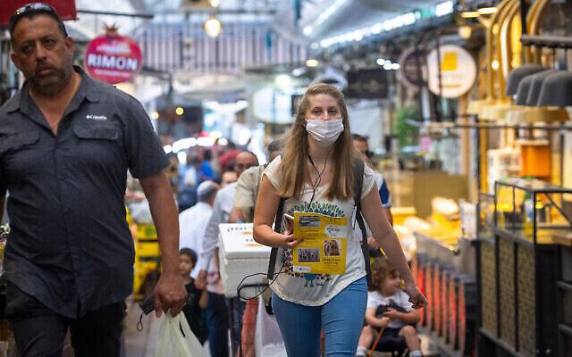 متسوقون يرتدون الكمامات في سوق محانيه يهودا في القدس، 26 مايو، 2021. (Olivier Fitoussi / Flash90)