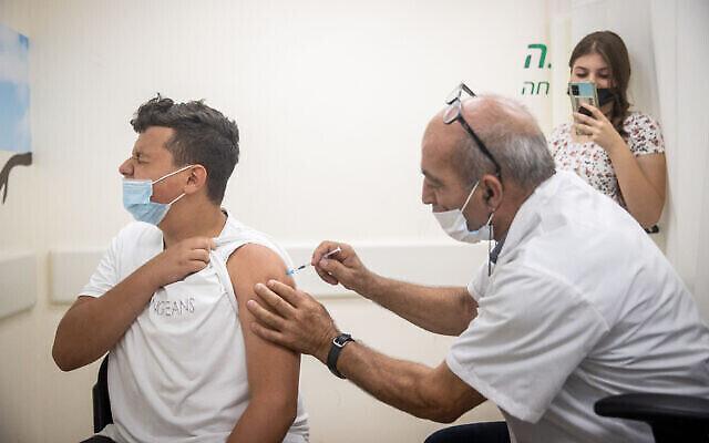 شاب اسرائيلي يتلقى لقاح ضد فيروس كورونا في مركز تطعيم تابع لصندوق المرضى كلاليت في القدس، 24 يونيو، 2021. (Yonatan Sindel / Flash90)