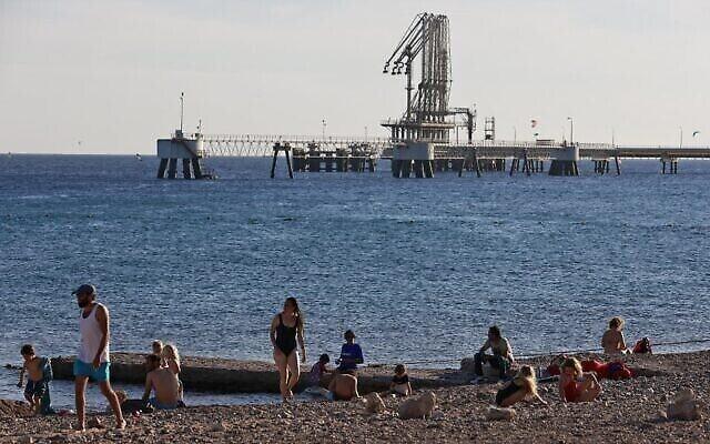"""إسرائيليون على شاطئ البحر الأحمر بالقرب من محطة النفط التابعة لشركة """"خطوط الأنابيب إيلات أشكلون"""" (EAPC) في مدينة إيلات الساحلية جنوب إسرائيل، 10 فبراير، 2021. (MENAHEM KAHANA / AFP)"""