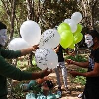 Masked Palestinian followers of the Hamas movement near Beit Lahia in the Gaza Strip, prepare to fly incendiary balloons across the northern border toward Israel, on May 8, 2021, a day after al-Quds (Jerusalem) Day. - Israel braced for more protests today after clashes at Jerusalem's flashpoint Al-Aqsa Mosque compound wounded more than 200 people and as the US, EU and regional powers urged calm after days of escalating violence. The unrest came as Iran and its allies around the world marked Al-Quds Day, an annual show of solidarity with the Palestinians. (Photo by MOHAMMED ABED / AFP)