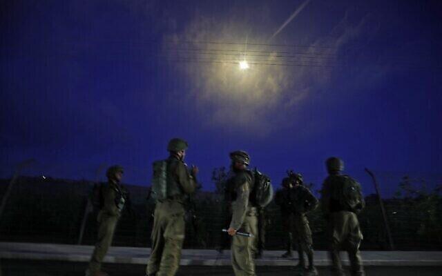جنود إسرائيليون يقومون بالحراسة بعد إطلاق قنابل إنارة فوق بلدة المطلة الشمالية، على الحدود مع لبنان، في أعقاب مظاهرة مؤيدة للفلسطينيين عبر الحدود في منطقة الخيام اللبنانية، 14 مايو، 2021. (Jalaa MAREY / AFP)