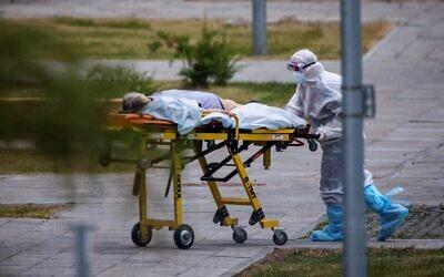 مسعف يرافق امرأة إلى مستشفى حيث يتم علاج المرضى المصابين بفيروس كورونا  في  كوموناركا خارج العاصمة الروسية موسكو في 30 يونيو 2021.  (Dimitar DILKOFF / AFP)
