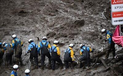 الشرطة تبحث عن المفقودين المدفونين تحت الوحل في موقع الانهيار الأرضي بعد أيام من هطول أمطار غزيرة في أتامي في مقاطعة شيزوكا، 5 يوليو، 2021.  ( CHARLY TRIBALLEAU / AFP)