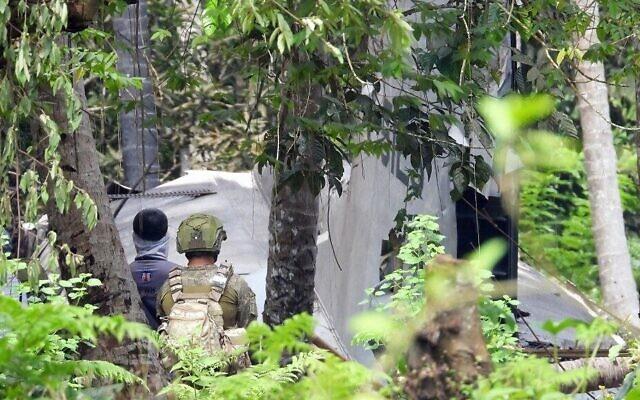 جنود فلبينيون يقفون بالقرب من حطام طائرة نقل تابعة للقوات الجوية الفلبينية من طراز C-130 ، والتي تحطمت في 4 يوليو، مما أسفر عن سقوط 50 قتيلا، في بلدة جولو بمقاطعة سولو بالقرب من جزيرة مينداناو  بجنوب البلاد،  5 يوليو، 2021.  (Nickee BUTLANGAN / AFP)