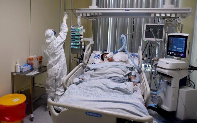 عامل طبي يرتدي  زيا واقيا يقدم العلاج مريض مصاب بفيروس كورونا في وحدة العناية المركزة في مستشفى مارينسكايا في سانت بطرسبرغ في 7 يوليو 2021.   ( Olga MALTSEVA / AFP)