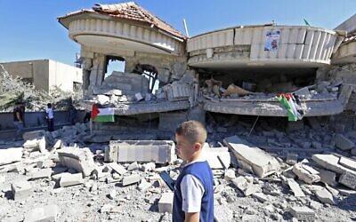 طفل فلسطيني يمر أمام مبنى يعود لمنتصر شلبي، المتهم بقتل طالب إسرائيلي في هجوم في مايو، بعد أن دمرته القوات الإسرائيلية في قرية ترمسعيا بالقرب من رام الله في الضفة الغربية، 8 يوليو، 2021.  (JAAFAR ASHTIYEH / AFP)
