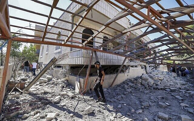 شاب فلسطيني يمر أمام مبنى يعود لمنتصر شلبي، المتهم بقتل طالب إسرائيلي في هجوم في مايو، بعد أن دمرته القوات الإسرائيلية في قرية ترمسعيا بالقرب من رام الله في الضفة الغربية، 8 يوليو، 2021.  (JAAFAR ASHTIYEH / AFP)