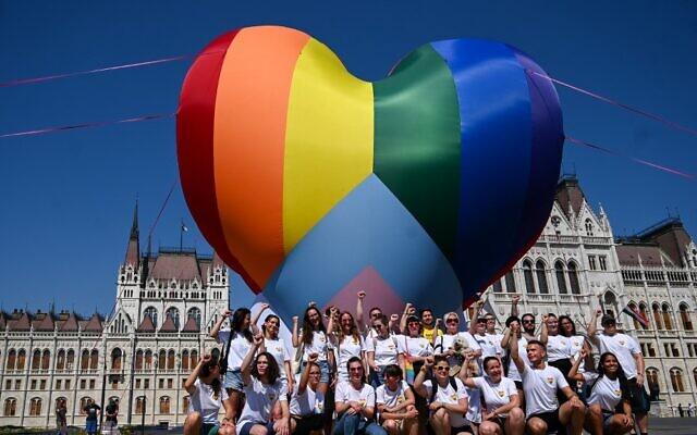 نشطاء يطلقون بالون عملاق على شكل قلب بألوان قوس قزح أثناء خلال احتجاج على قانون جديد حظر نشر محتويات عن المثلية بين القاصرين أمام البرلمان في بودابست، 8 يوليو، 2021.   (  ATTILA KISBENEDEK / AFP)