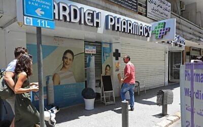 أشخاص يسيرون من أمام باب مغلق لصيدلية في العاصمة اللبنانية بيروت، خلال إضراب على مستوى البلاد للصيدليات احتجاجا على النقص الحاد في الأدوية، 9 يوليو، 2021. (Anwar AMRO / AFP)