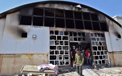 تجمع الناس في  عنبر عزل مرضى فيروس كورونا في مستشفى الحسين بعد اندلاع حريق هائل، مدينة الناصرية جنوب العراق، 13 يوليو، 2021. ( Asaad NIAZI / AFP)