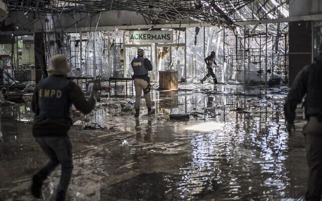 إطلاق النار على لص مشتبه به من قبل عناصر الشرطة خلال دورية داخل مركز تجاري غمرته المياه في فوسلوروس، جنوب إفريقيا، 13 يوليو، 2021. .  (MARCO LONGARI / AFP)