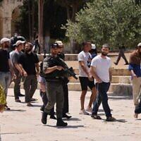 """قوات الأمن الإسرائيلية توفر الحراسة لمجموعة من اليهود عند دخولها إلى الحرم القدسي في البلدة القديمة بالقدس، خلال يوم الصوم """"تيشعا بآف"""" الذي يحيي فيه اليهود ذكرى خراب الهيكلين، 18 يوليو، 2021. (Ahmad Gharabli/AFP)"""