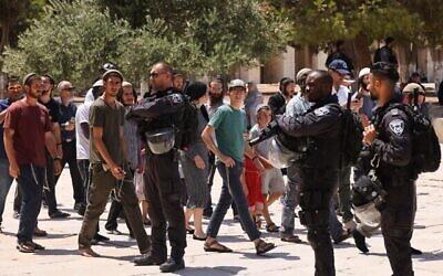 """الشرطة الإسرائيلية تحرس مجموعة من اليهود عند مدخل الحرم القدسي في البلدة القديمة بالقدس، خلال يوم الصوم """"تشعا بآف"""" الذي يحيي ذكرى خراب الهيكلين، 18 يوليو، 2021. (Ahmad Gharabli / AFP)"""