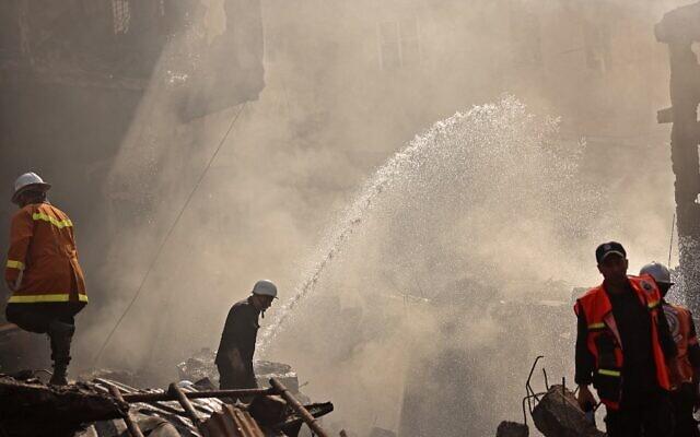 عناصر إنقاذ إطفاء فلسطينية في موقع انفجار وقع في مدينة غزة، لم يتم تحديد سببه بعد، 22 يوليو، 2021. (MOHAMMED ABED / AFP)