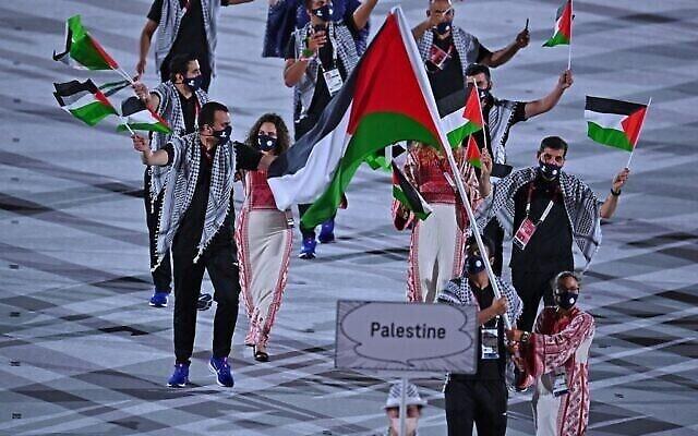 حاملة العلم الفلسطيني دانيا نور والوفد المرافق لها خلال حفل افتتاح دورة الالعاب الاولمبية طوكيو 2020، في الاستاد الاولمبي في طوكيو، 23 يوليو، 2021. (Ben STANSALL / AFP)