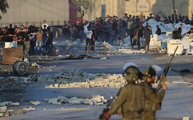 اشتباكات بين متظاهرين فلسطينيين والجنود الإسرائيليين يطالبون الجيش بتسليم جثة رجل قُتل برصاص القوات الإسرائيلية الليلة الماضية ، في قرية بيتا بالضفة الغربية، 28 يوليو، 2021.( by JAAFAR ASHTIYEH / AFP)