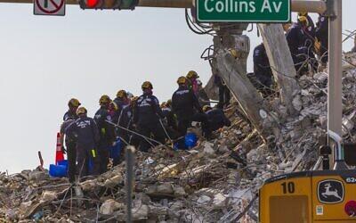عمال الإنقاذ يواصلون جهود البحث  بعد أن انهيار برج 'تشامبرلين' المكون من 12 طابقا والذي انهار جزئيا  قبل أن تقوم السلطات بهدم ما تبقى منه  في 5 يوليو 2021 في مدينة سيرفسايد بولاية فلوريدا. جاء قرار المسؤولين بهدم بقية المبنى بسبب اقتراب العاصفة الاستوائية إلسا والمخاوف من أن الهيكل قد ينهار بطريقة غير خاضعة للرقابة.(Photo by Saul MARTINEZ / GETTY IMAGES NORTH AMERICA / Getty Images via AFP)